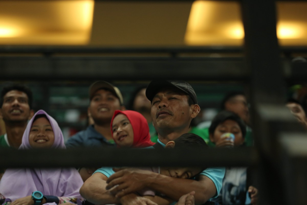 Salah satu Bonek sedang menyaksikan pertandingan bersama anaknya